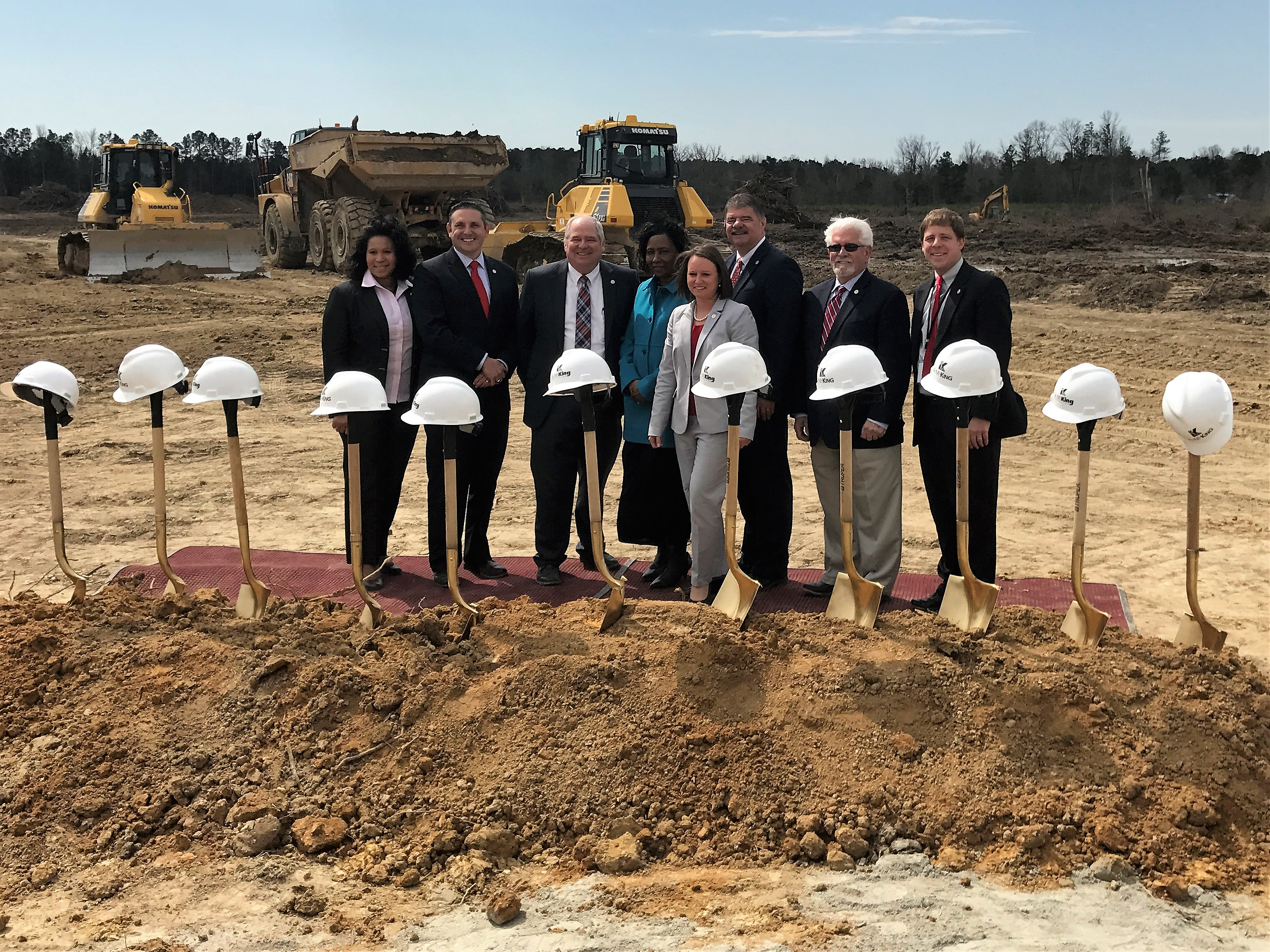 Image of board members behind shovels at a groundbreaking