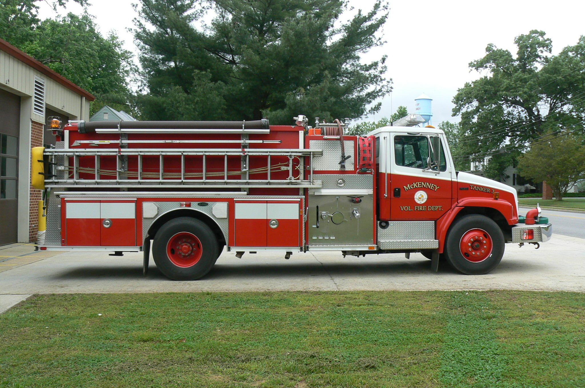Red fire tanker truck with ladder