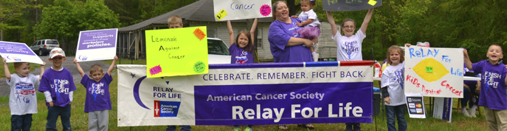 Nine children and one adult with Relay for Life signs